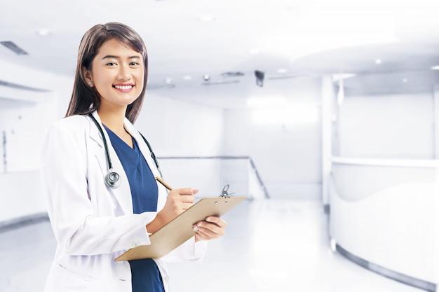 Aziatische vrouw arts in wit laboratoriumlaag en stethoscoopholdingsklembord