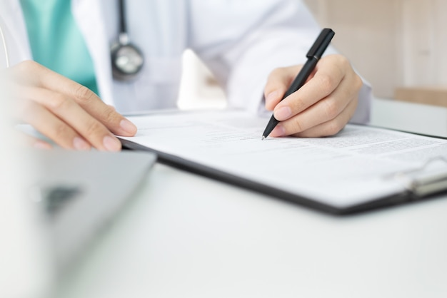 Aziatische vrouw arts met groene doek en laboratoriumlaag die en nota informatie over een klembord werken nemen.