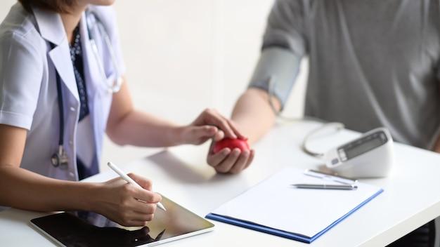Aziatische vrouw arts met tablet die aan mannelijke aziatische patiënt in bureau spreekt