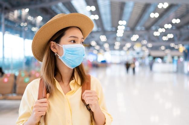 Aziatische vrouw backpacker die gezichtsmasker draagt die in luchthaven loopt als nieuwe normale reisregel en sociaal afstandsconcept