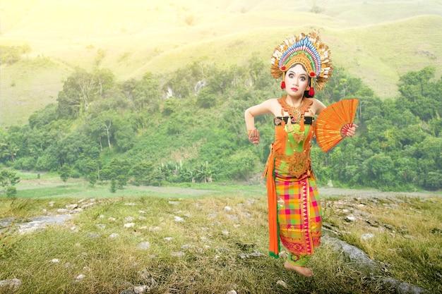 Aziatische vrouw balinese traditionele dans (kembang girang-dans) dansen op het veld