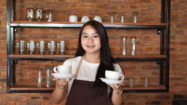 Aziatische vrouw barista bedrijf kopje koffie