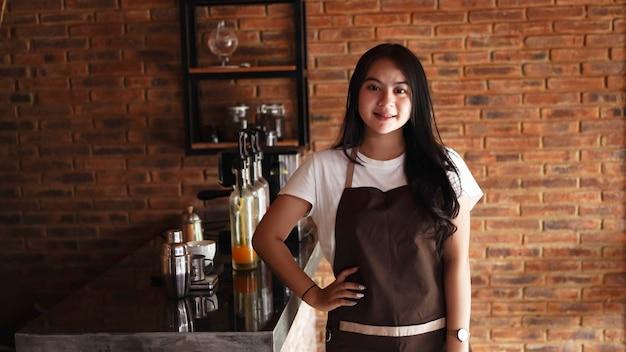 Aziatische vrouw barista smilling camera kijken in café