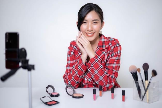 Aziatische vrouw beauty blogger maakt make-up, beoordelingen schoonheidsproduct voor videoblog