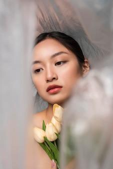 Aziatische vrouw bedekt met plastic met een boeket bloemen