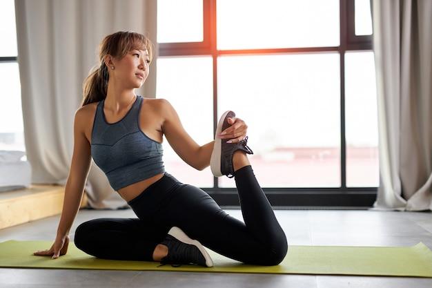 Aziatische vrouw benen strekken, oefeningen op de mat, training. gezonde levensstijl en sportconcept