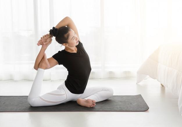 Aziatische vrouw beoefenen van yoga, doen zeemeermin oefening of eka pada rajakapotasana poseren in de slaapkamer