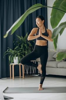 Aziatische vrouw beoefent yoga thuis
