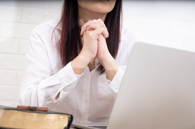 Aziatische vrouw bidden door geloof met computerlaptop, online concept van kerkdiensten