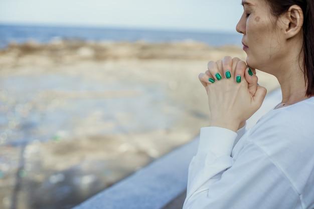 Aziatische vrouw bidden tot god buiten.