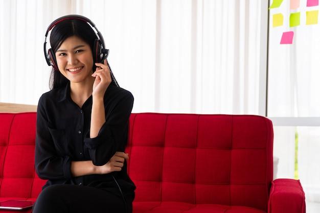 Aziatische vrouw blogger influencer zittend op de bank met koptelefoon op