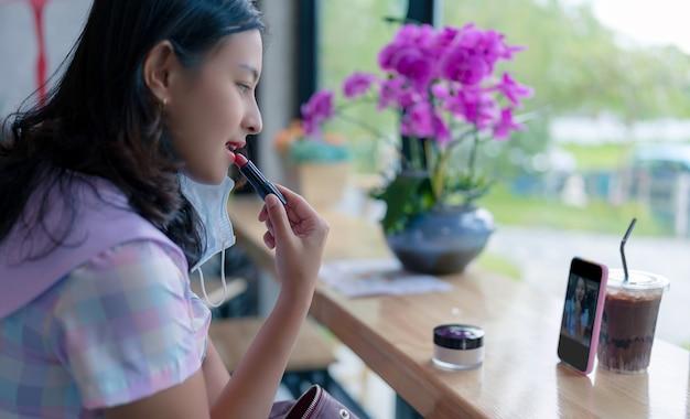 Aziatische vrouw brengt rode lippenstift op lippen aan in café met smartphone als spiegel, meisje drinkt wat en make-up aan houten tafel in coffeeshop