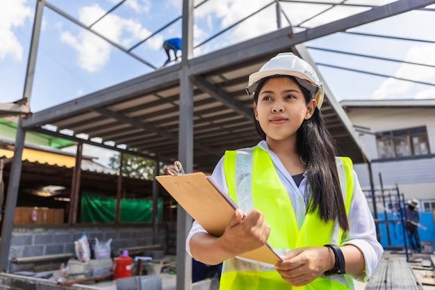 Aziatische vrouw burgerlijk ingenieur papier plan gebouw architect dragen witte veiligheidshelm kijken naar bouwplaats.