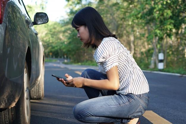Aziatische vrouw controleer op kapotte auto's op de wegen rond het bos.