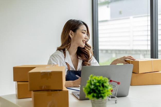 Aziatische vrouw controleert pakketdozen voor klanten, ze heeft een online winkel, ze neemt bestellingen van klanten op de website aan en stuurt ze via een privékoerierdienst. online verkoopconcept.