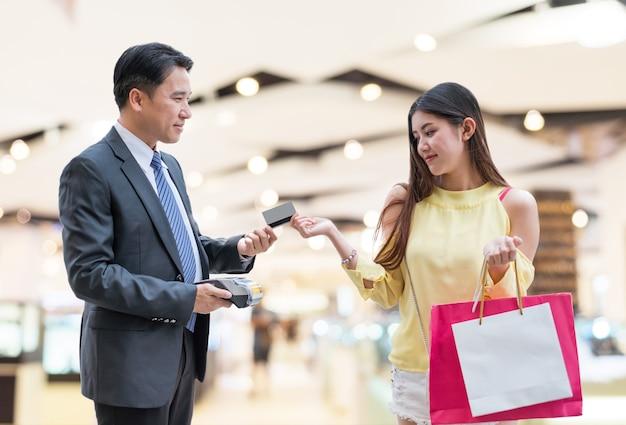 Aziatische vrouw creditcard betalen met betaalterminal en kassier man bij warenhuis