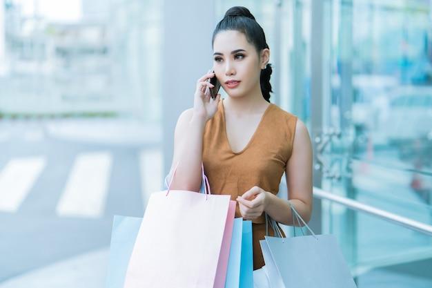 Aziatische vrouw de telefoon is momenteel te koop. warenhuis