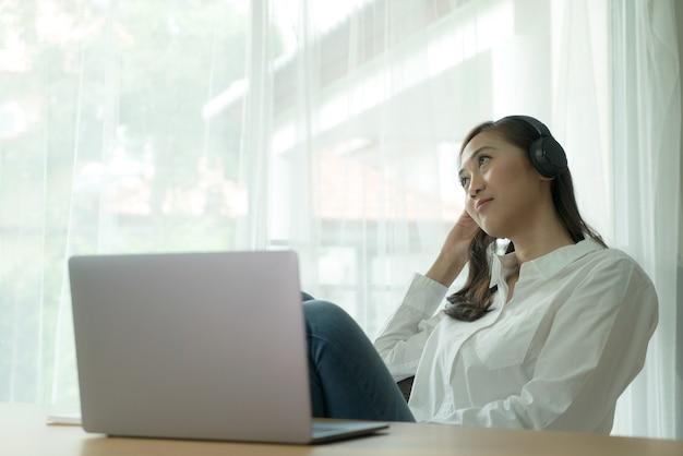 Aziatische vrouw die aan een koptelefoon en laptop werkt die buiten het raam kijkt om te ontspannen en een pauze te nemen