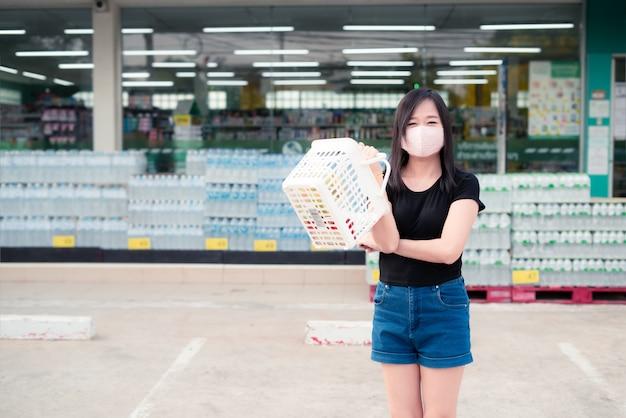 Aziatische vrouw die aan een supermarkt met een beschermend gezichtsmasker winkelt en een mand houdt