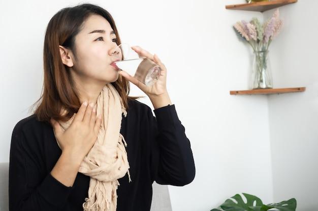 Aziatische vrouw die aan keelpijn lijdt die warm water drinkt