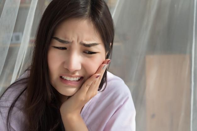 Aziatische vrouw die aan kiespijn of pijn van de tandgevoeligheid lijdt