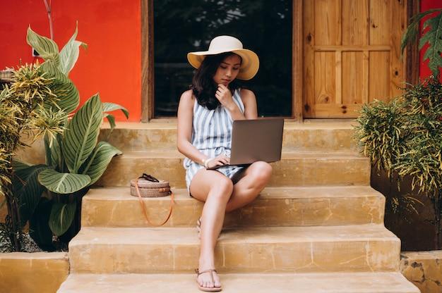Aziatische vrouw die aan laptop op een vakantie werkt en op de treden zit