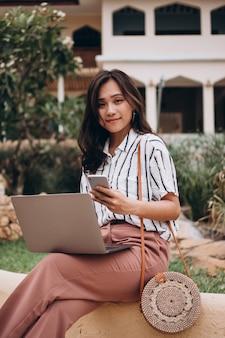 Aziatische vrouw die aan laptop op een vakantie werkt
