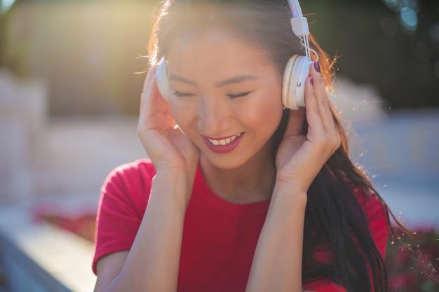 Aziatische vrouw die aan muziek luistert