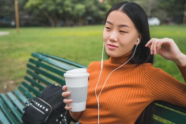 Aziatische vrouw die aan muziek luistert.