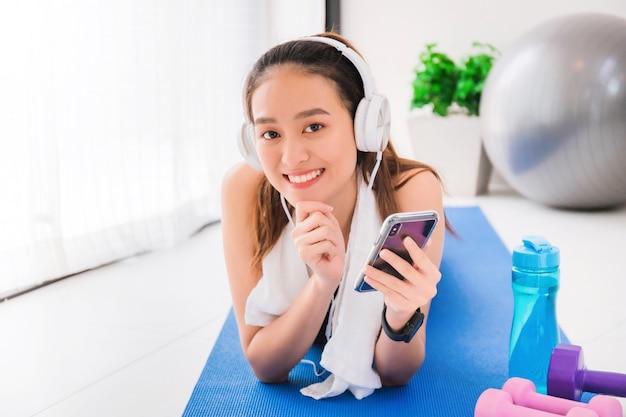 Aziatische vrouw die aan muziek met hoofdtelefoon en smartphone na oefening thuis luistert.