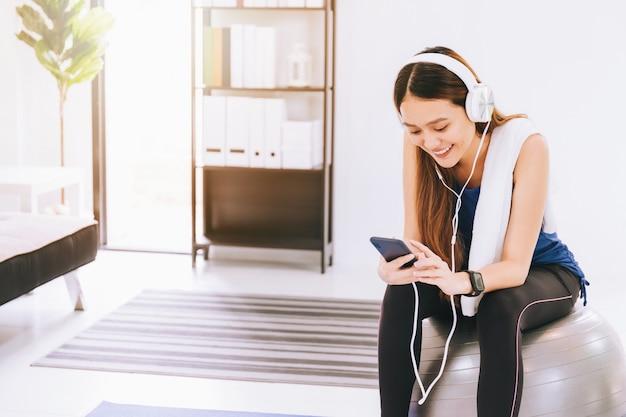 Aziatische vrouw die aan muziek met hoofdtelefoon en smartphone na spelyoga luisteren en thuis oefenen