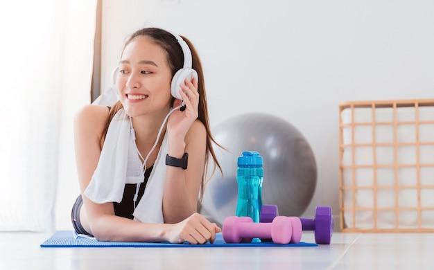 Aziatische vrouw die aan muziek met hoofdtelefoon na spel yoga en oefening thuis luisteren