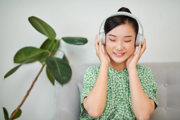 Aziatische vrouw die aan muziek met hoofdtelefoons thuis luistert draadloze technologie