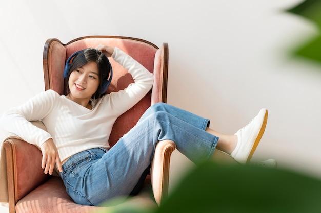Aziatische vrouw die aan muziek op een rode bank luistert