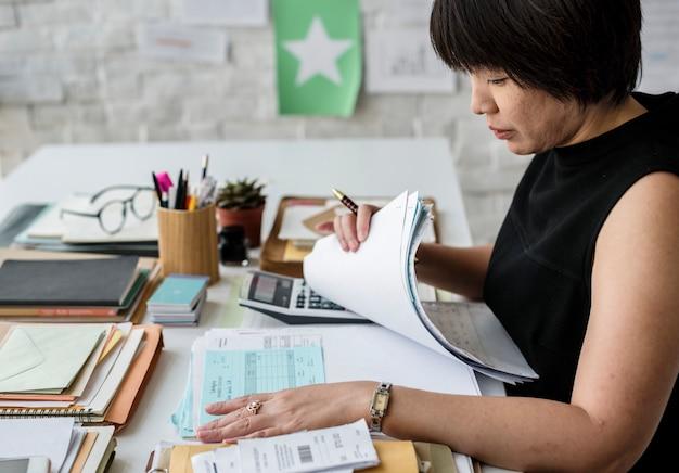 Aziatische vrouw die aan rekeningen werkt