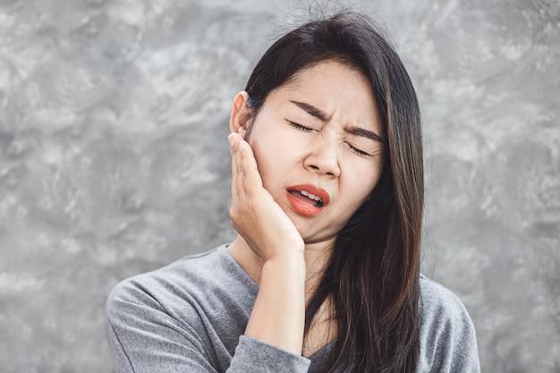 Aziatische vrouw die aan tandpijnprobleem lijdt