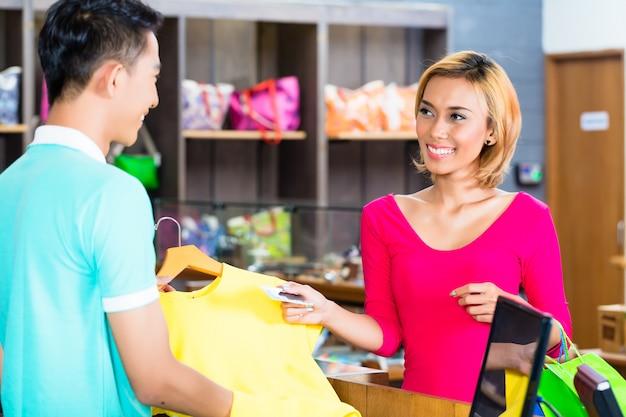Aziatische vrouw die aankoop in manieropslag betaalt