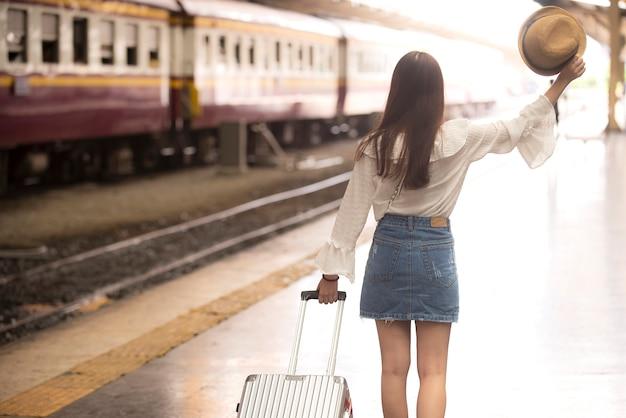 Aziatische vrouw die achteruitgaat dragende bagage bij het stationplatform