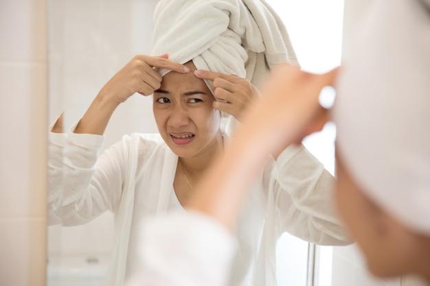Aziatische vrouw die acne op haar voorhoofd drukt