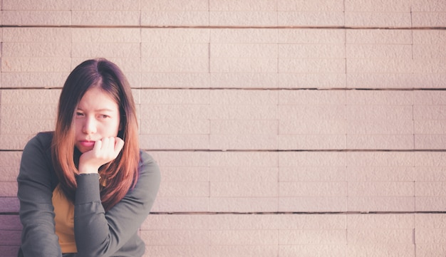 Aziatische vrouw die alleen en depressief zit, portret van vermoeide jonge vrouw, depressie