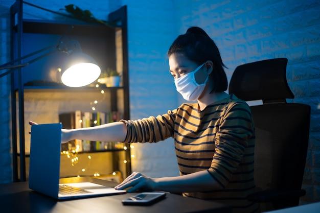 Aziatische vrouw die beschermend gezichtsmasker draagt dat aan laptop overuren thuis werkt. . werk vanuit huis om het coronavirus covid 19-concept te vermijden.