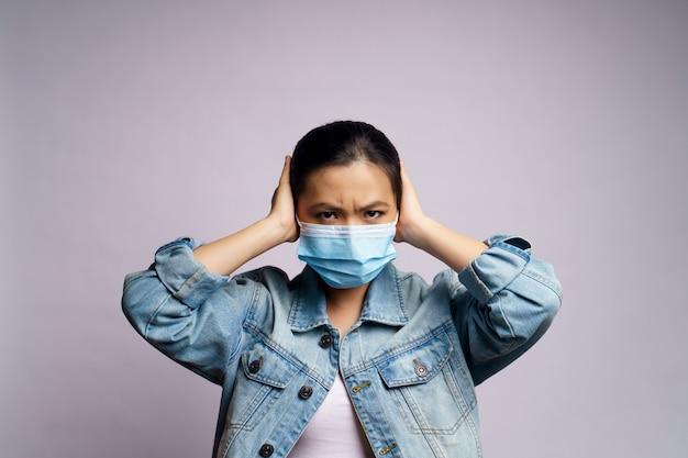 Aziatische vrouw die beschermend gezichtsmasker draagt en haar oren behandelt door geïsoleerde handen.