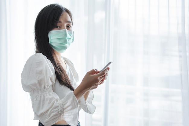 Aziatische vrouw die beschermend gezichtsmasker draagt en mobiele smartphone gebruikt