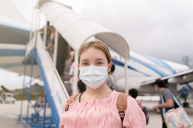 Aziatische vrouw die beschermend gezichtsmasker draagt tijdens covid-19-viruspandemie, loopt naar de trap die het vliegtuig binnengaat, parkeren buiten de terminal op de luchthaven.