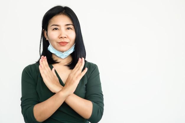 Aziatische vrouw die beschermend gezichtsmasker op verkeerde manieren draagt