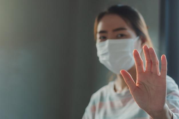 Aziatische vrouw die beschermend hygiënemasker draagt