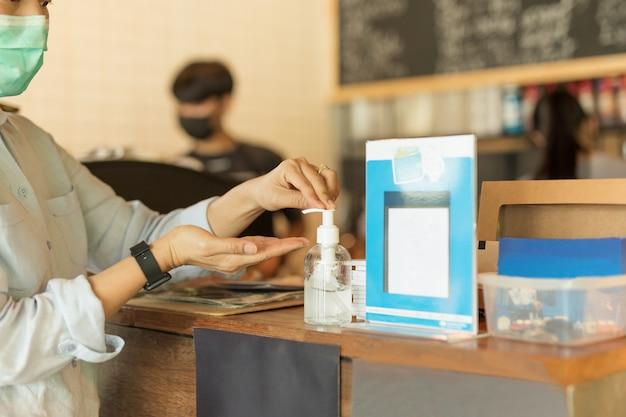 Aziatische vrouw die beschermend masker draagt dat alcohol antiseptische gel gebruikt voorkomt uitbraak van covid-19 in koffie.