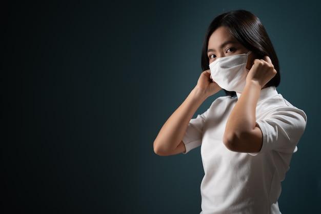 Aziatische vrouw die beschermend masker draagt voor bescherming tegen virussen en ziekten die op blauw worden geïsoleerd