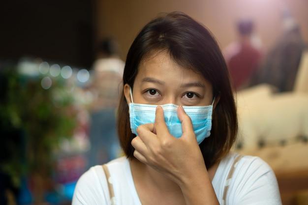 Aziatische vrouw die beschermend masker op haar gezicht draagt