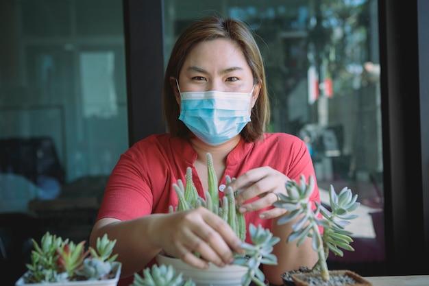 Aziatische vrouw die beschermingsmasker draagt dat cactus thuis plant